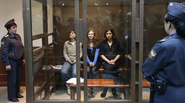 Members of Pussy Riot sit in the defendants' cage in a Moscow court room.