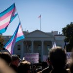 Trans flag flying in crowd in front of the White House